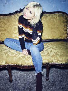Die Sängerin Dido auf einer Couch